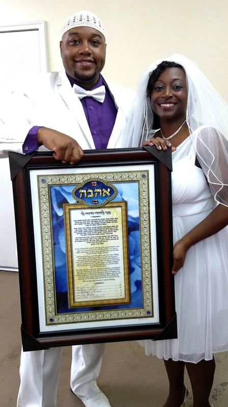 "Briana and Yair David with their framed custom ketubah ""Love in Bloom Blue"" by Ashra Designs"